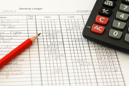 鉛筆と電卓を使って簿記を示す手書きの会計元帳。
