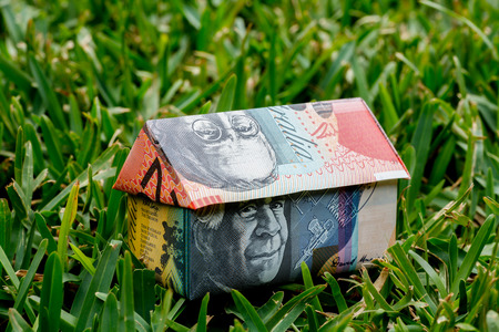 Origami house made with Australian Notes sitting on freen grass Stock Photo