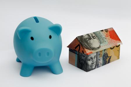 Origami money house next to a blue piggy bank