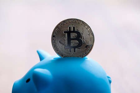 Large Bitcoin being deposited into a piggy bank