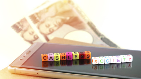 Cashless society-concept met alfabet, smartphone voor elektronische betaling en online zakelijke transacties