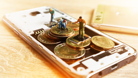 Three miniature mini  figures with keep money in mobile. Cashless Society Concept pay with Application mobile phone Stock Photo