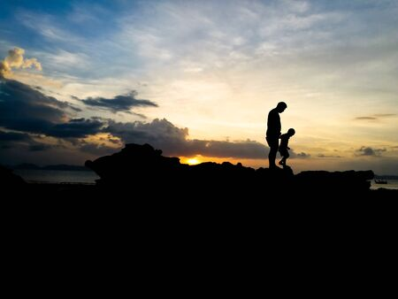 Silhouette of loving father and son walked on seaside and beautiful sunset background
