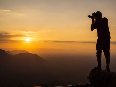 A photographer standing on the top of the hill At sunrise, there are clouds, fog at Pha Mor Daeng, Sisaket Province, Thailand, ASIA. Banque d'images - 132557321