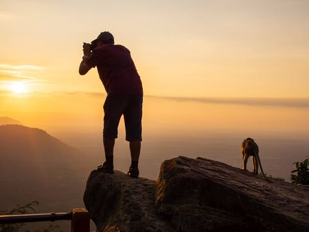 A photographer standing on the top of the hill At sunrise, there are clouds, fog at Pha Mor Daeng, Sisaket Province, Thailand, ASIA. Banque d'images - 132557190