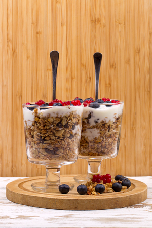 bramble: Two ice-cream bowls with a dessert. Yogurt, muesli and  fresh berries of blueberry, bog bilberry  and stone bramble. Stock Photo