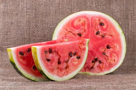 sliced watermelon: Closeup on sliced watermelon on a table on burlap Stock Photo