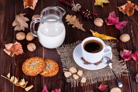 granos de cafe: Taza de café, crema, granos de café y galletas de avena en una mesa