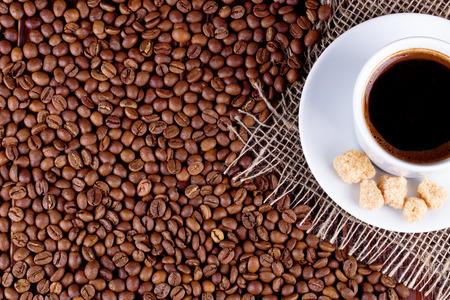 granos de cafe: Taza de café en un platillo y granos de café sobre una mesa
