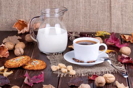 granos de cafe: Taza de caf�, crema, granos de caf� y galletas de avena en una mesa