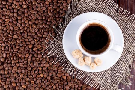 granos de cafe: Taza de caf� en un platillo y granos de caf� sobre una mesa