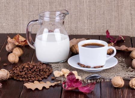 granos de cafe: Taza de café, crema, granos de café y caña de azúcar en una mesa