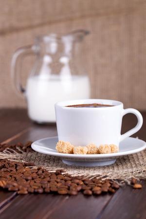 granos de cafe: Taza de caf�, crema, granos de caf� y ca�a de az�car en una mesa
