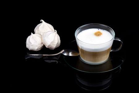 Cappuccino with meringue in a glass cup on a black table