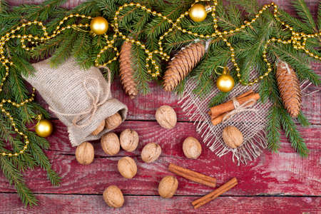 fir cones: Walnuts, cinnamon and fir cones on a wooden background