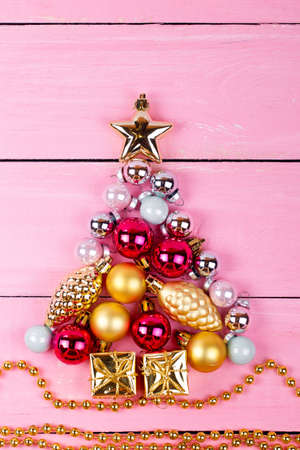 christmas tree ball: Brilliant christmas baubles and ornaments  in the form of a fir on a pink table