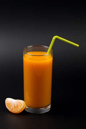 sweet segments: Segments of tangerine and juice in a glass on a black background