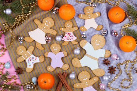 balls decorated: Homemade baked Christmas gingerbread man on vintage wooden background. Anise, cinnamon and decoration utensils.