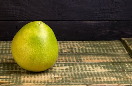 pummelo: Fruit of a pummelo on an old wooden table Stock Photo