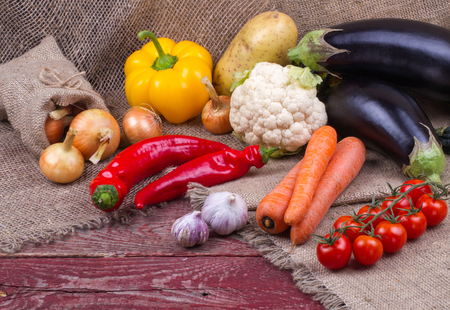 harvest: Eggplants, cauliflower, pepper, carrots, tomatoes, potatoes, onions and garlic on a wooden table