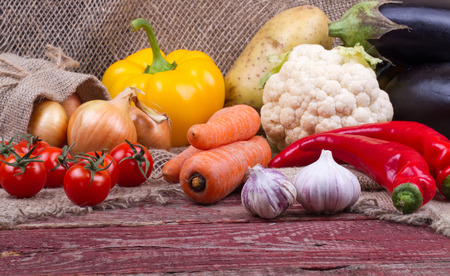 onion: Eggplants, cauliflower, pepper, carrots, tomatoes, potatoes, onions and garlic on a wooden table