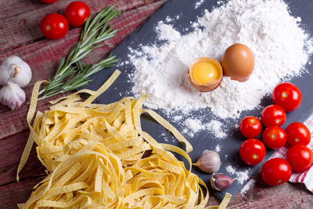 Fettuccine paste, egg, flour, garlic, cherry tomato and rosemary on a chopping board. Top view Stock Photo