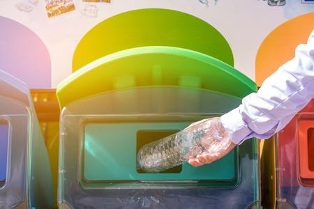 Selective focus hand throwing empty plastic bottle into the trash. Standard-Bild