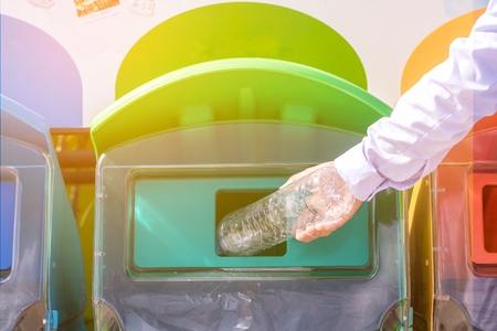 Selective focus hand throwing empty plastic bottle into the trash. Banque d'images