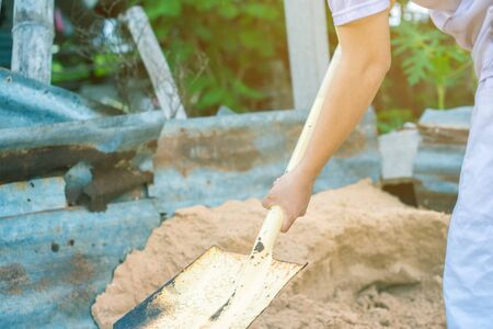 Selective focus man with shovel digging garden bed or farm.