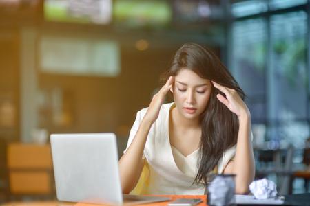 ノート パソコンと疲れの若いビジネス女性。