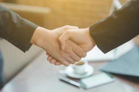 実業家と握手をするビジネスマン握手、会議を仕上げ、揺れ手成功取引、若い実業家行く-挨拶、取引、合併と買収の概念