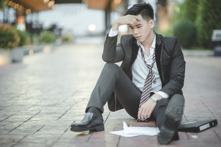 dismissed: Tired or stressed businessman sitting on the walkway in the city after his work. Image of Stressed businessman concept, young caucasian businessman tired from work sitting at stairs, unemployment.