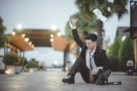 Tired or stressed businessman sitting on the walkway in the city after his work. Image of Stressed businessman concept, young caucasian businessman tired from work sitting at stairs, unemployment.