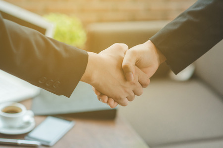 Business people shaking hands, finishing up a meeting, shaking hands success deal, Young businesswoman going to make handshake with a businessman -greeting, dealing, merger and acquisition concepts Standard-Bild