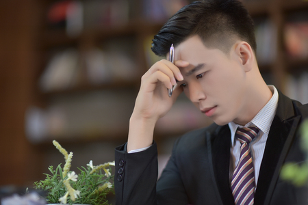 Young attractive Asian business man sleeping, drowsing or taking a nap at her desk, Tired business man accountant with bills and paper folders in office, tired young business woman with laptop. Standard-Bild