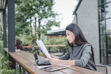 Business woman working in coffee shop with documents Standard-Bild - 106454179