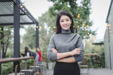 Portrait of young beautiful business woman in the office. Crossed arms Standard-Bild - 106389154