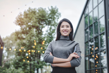 Portrait of young beautiful business woman in the office. Crossed arms Standard-Bild