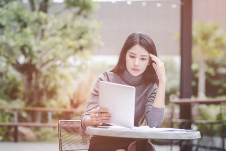 Business woman holding a tablet computer stressed because of falling stock Standard-Bild
