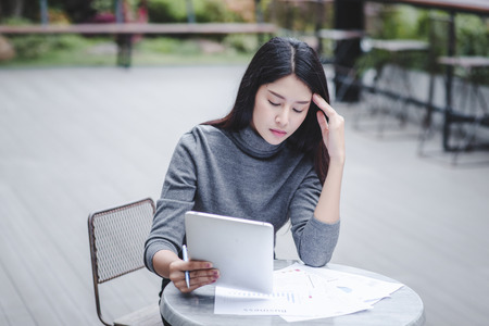 Business woman holding a tablet computer stressed because of falling stock Standard-Bild - 106389092