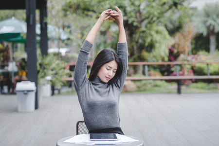 Portrait of young smiling woman sitting at home office desk in front of laptop  stretching with enjoyment after the work is done  looking at screen with happy expression Standard-Bild