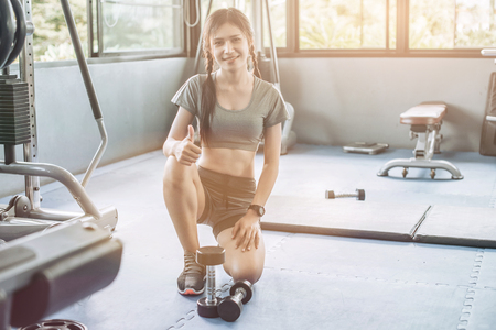 young asian pretty woman doing exercises with dumbbell at biceps in fitness gym with people background, bodybuilder, healthy lifestyle, exercise fitness, workout and sport training concept, soft focus