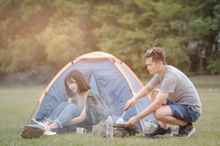 man and woman sitting in chairs outside the tent. Couple camping in nature