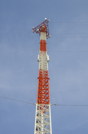 Cell phone tower rises against a blue sky, Used to transmit telephony signal.