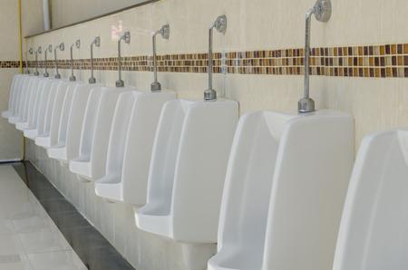 row of outdoor urinals men public toilet,Closeup white urinals in mens bathroom, design of white ceramic urinals for men