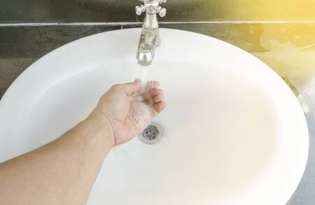 toilet: Hands being washed in sink under running water with freckled forearms