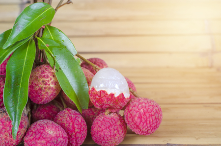Lychee, Fresh lychee and peeled showing the red skin and white flesh with green leaf on a bamboo wooden background