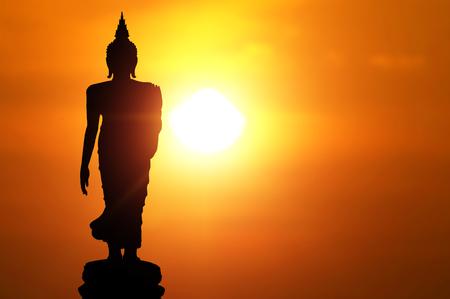 Magha Asanha Visakha Puja Day, Silhouette Buddha su sfondo tramonto dorato.