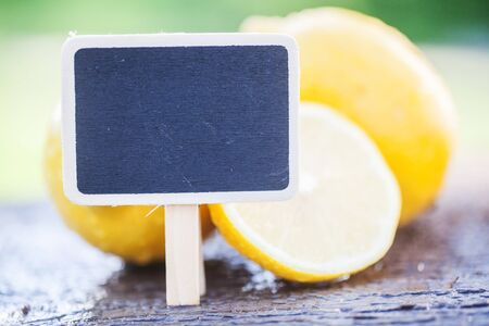 Lemon and chalk wooden board on green natural background Фото со стока