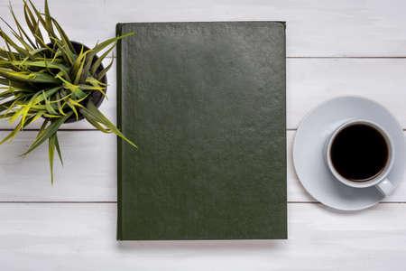 Book, cup black tea or coffee, top view on wooden background, desk. Standard-Bild